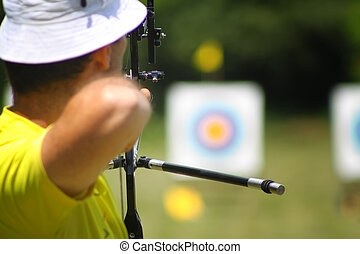 Aiming archer on archery range is concentrated and ready to...