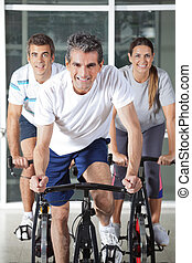 Men And Woman On Spinning Bikes - Happy men and woman on...