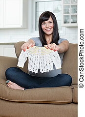Pregnant Woman Holding Baby Clothing On Sofa - Portrait of...