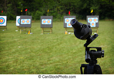 Monocular fixed on tripod on archery range during...
