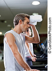 Man Wiping Sweat With Towel At Health Club - Side view of...