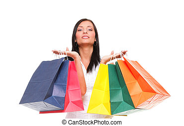 Portrait of young woman carrying shopping bags against white...