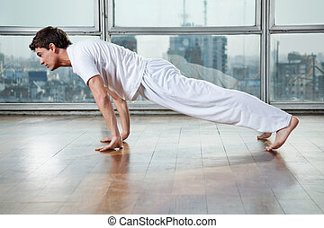 Young Man Practicing Yoga At Gym - Side view of young man...