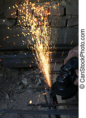 Worker cutting metal with many sharp sparks