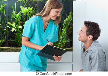 Dentist Taking An Appointment Of Man - Happy female dentist...