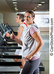 Woman And Man Running On Treadmill - Side view of happy...