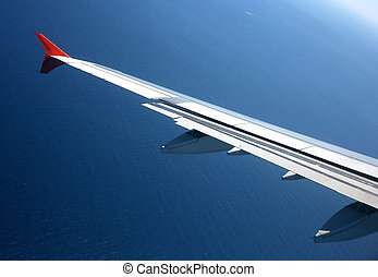 Wing of the plane on a background of sea