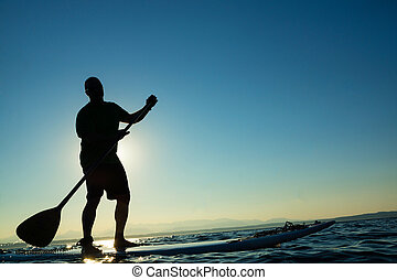 Stand Up Paddle Board-Man - Man paddling stand up paddle...