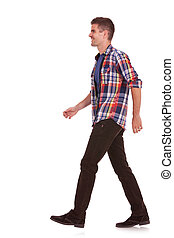 side view of man walking - side view of a young casual man...