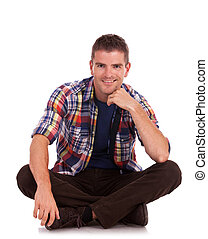 young man sitting and smiling - young casual man sitting on...