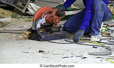 Worker in workwear cutting metal reinforcing bar with...