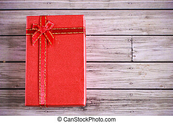 Red present box on wooden background