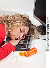 Exhausted woman asleep at work - with spilled energy pills