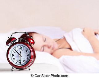 Young sleeping woman and alarm clock in bedroom at home.