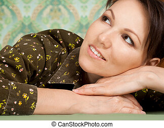 Nice woman dreaming on a green background