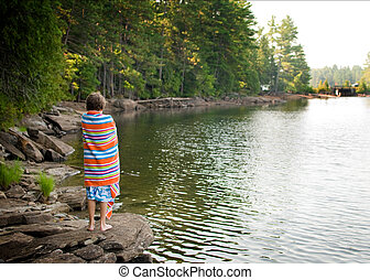 boy wrapped in a beach towel at a lake in Haliburton County