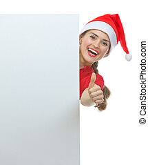 Young woman in Christmas hat looking out from blank billboard and showing thumbs up