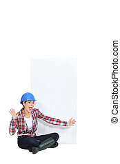 Expressive female construction worker with a blank board
