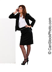 Businesswoman talking on her mobile phone and leaning...