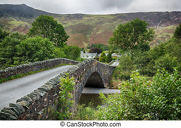 Bridge over small river at Grange in Lake District -...