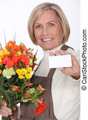Middle-aged female florist holding out business card