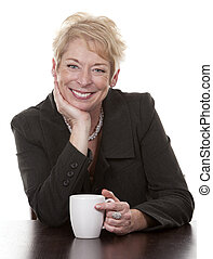 woman with coffee - mature woman sitting down having a cup...