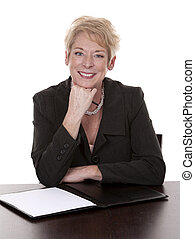 business woman - mature woman sitting behind desk and...