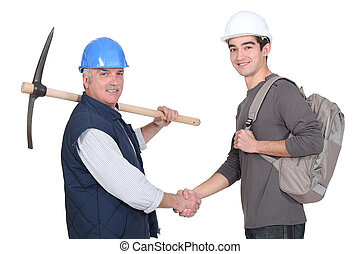 Laborer welcoming young teenage apprentice