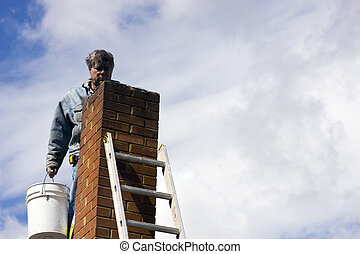 chimney repair - brick mason on a ladder repairing damaged...