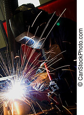 Welder welding metal - Welder welding a car chasis in...