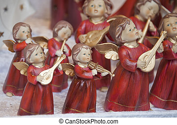 christmas angels in red dressed playing instruments