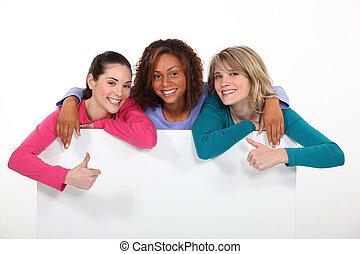Three girls behind white panel