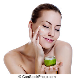 Happy smiling beautiful woman applying moisturizer cream on...