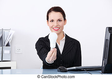 Woman in office holding energy saving bulb