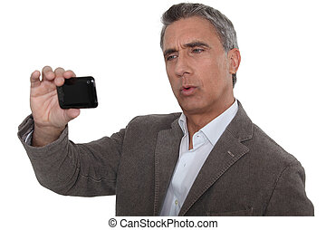 businessman watching something on his cell phone