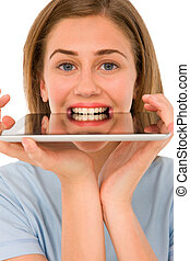 teenage girl with tablet in mouth