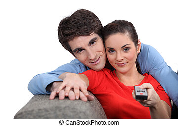 Couple sitting on a sofa with a remote control