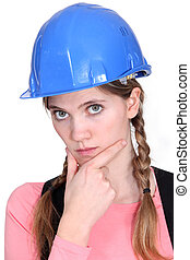 A pensive female construction worker.