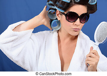Woman with her hair in rollers holding a brush and wearing...