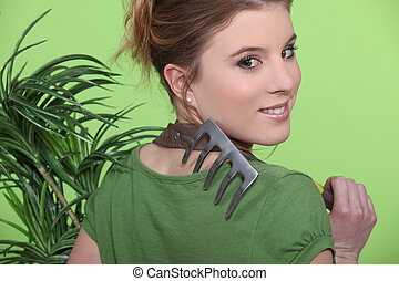 Female gardener carrying rake