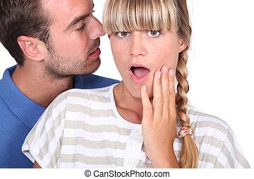 man telling a secret to a woman
