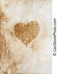 Burnt heart silhouette on the aged paper