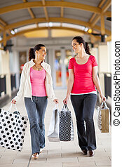 women walking with shopping bags - two young women walking...