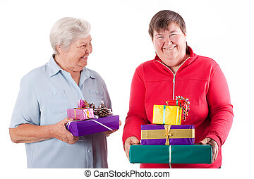 Female senior and mental disabled woman holding gifts -...
