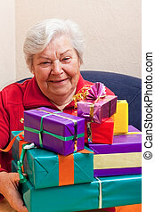 Senior sits and gets or give many gifts - female Senior sits...