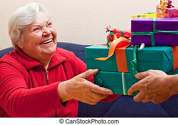 female Senior sits and gets or give many presents - a female...