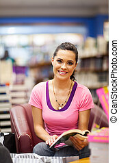 young woman reading book in bookstore