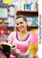 young woman reading a book in library
