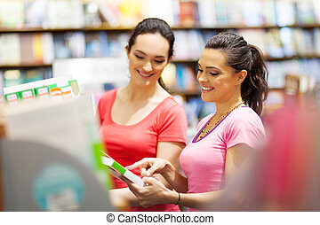 two young woman choosing a book in bookstore or library