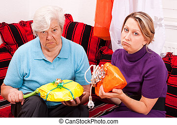 old and young woman getting loveless gifts - old and young...